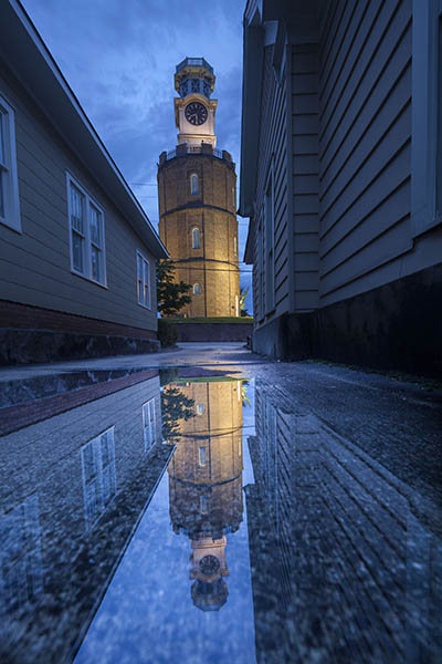 Clocktower Reflected In Rain Puddle